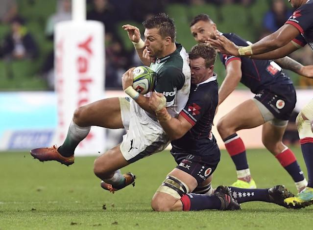 Bulls player Handre Pollard is tackled by Rebels player Angus Cottrell (AFP Photo/WILLIAM WEST)