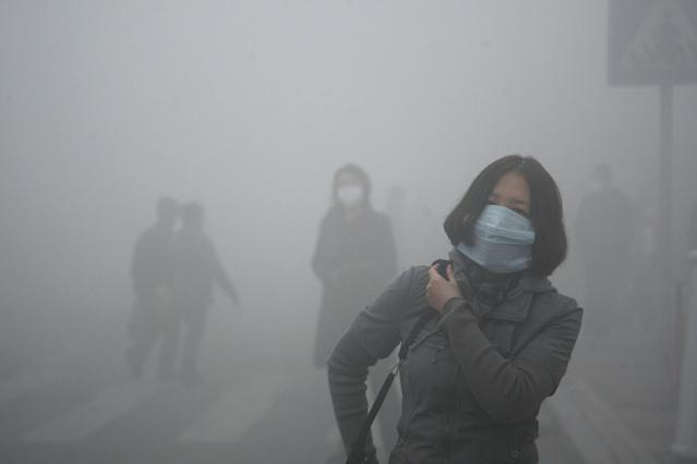 A woman wearing a mask walk through a street covered by dense smog in Harbin, northern China, Monday, Oct. 21, 2013. Visibility shrank to less than half a football field and small-particle pollution soared to a record 40 times higher than an international safety standard in one northern Chinese city as the region entered its high-smog season. (AP Photo/Kyodo News) JAPAN OUT, CREDIT MANDATORY