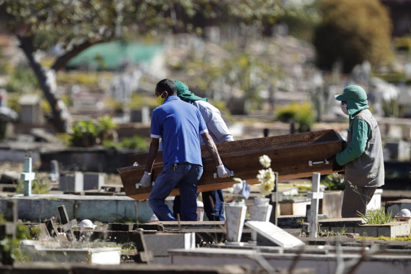 Cemetery workers carry the coffin of Bruno Correia, whose family said died of COVID-19, to his gravesite at the Campo da Esperanca cemetery in the Taguatinga neighborhood of Brasilia, Brazil, Friday, July 17, 2020. Brazil is nearing 2 million cases of COVID-19 and 75,000 deaths. (AP Photo/Eraldo Peres)