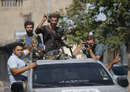 Turkish-backed Syrian opposition fighters cheer from a car as they drive around the border town of Akcakale, Sanliurfa province, southeastern Turkey, on their way to Tal Abyad, Syria, Monday, Oct. 14, 2019. Syrian troops entered Monday several northern towns and villages getting close to the Turkish border as Turkey's army and opposition forces backed by Ankara marched south in the same direction raising concerns of a clash between the two sides as Turkey's invasion of northern Syria entered its sixth day. (AP Photo/Lefteris Pitarakis)