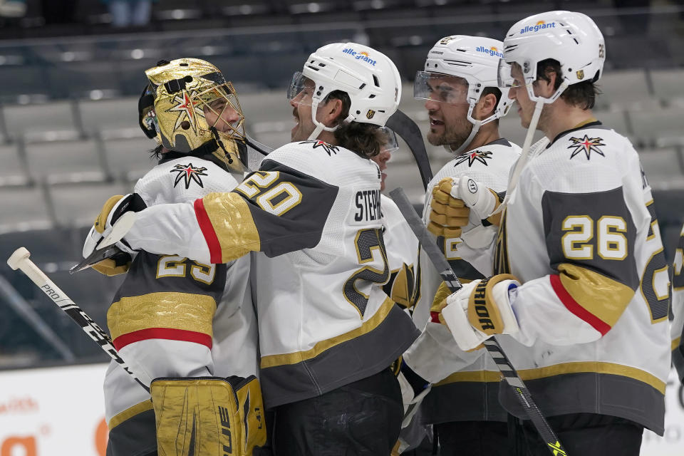 Vegas Golden Knights goaltender Marc-Andre Fleury, left, celebrates with Chandler Stephenson, William Carrier and Mattias Janmarkright, after the Golden Knights defeated the San Jose Sharks in an NHL hockey game in San Jose, Calif., Wednesday, May 12, 2021. (AP Photo/Jeff Chiu)