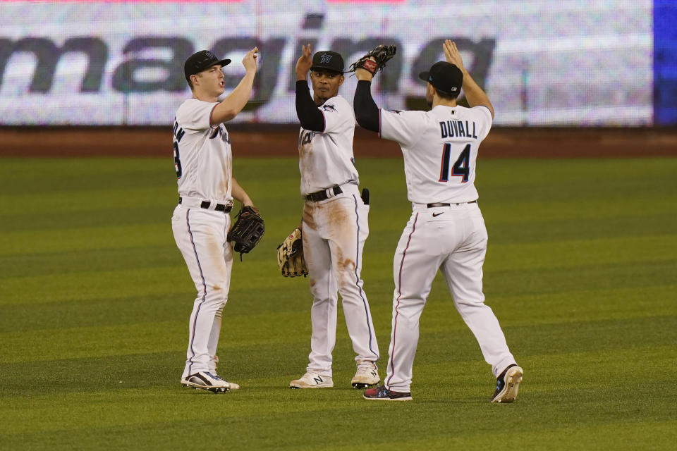 Miami Marlins' Corey Dickerson, left, Magneuris Sierra, center, and Adam Duvall celebrate after they defeated the Philadelphia Phillies in a baseball game, Monday, May 24, 2021, in Miami. (AP Photo/Wilfredo Lee)
