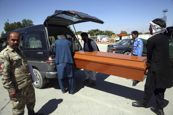 Families receive bodies of their relatives drowned after their boat sank in Turkey's Lake Van, at the Hamid Karzai International Airport in Kabul, Afghanistan, Wednesday, July 22, 2020. The boat sank last month while ferrying dozens of migrants across a lake in eastern Turkey. (AP Photo/Rahmat Gul)