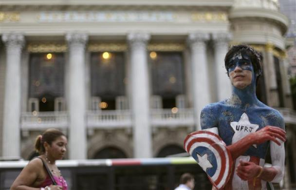 """A high school graduate, painted as Captain America for his initiation into Rio de Janeiro Federal University (UFRJ) during the traditional """"trote"""", stands in Cinelandia Square in Rio de Janeiro March 15, 2011. The students used Captain America as the theme as the city awaits President Barack Obama's state visit on March 20."""