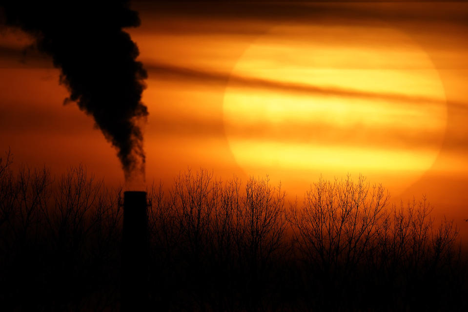 Emissions from a coal-fired power plant are silhouetted against the setting sun, Monday, Feb. 1, 2021, in Independence, Mo. (AP Photo/Charlie Riedel)