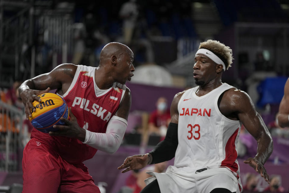 Poland's Michael Hicks, left, looks to pass around Japan's Ira Brown (33) during a men's 3-on-3 basketball game at the 2020 Summer Olympics, Saturday, July 24, 2021, in Tokyo, Japan. (AP Photo/Jeff Roberson)