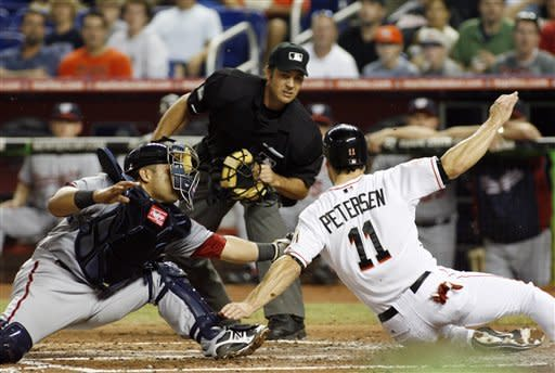 Miami Marlins' Bryan Petersen attempts to score but is tagged out by Washington Nationals catcher Jhonatan Solano during the second inning of a baseball game in Miami, Wednesday, May 30, 2012. (AP Photo/Jeffrey Boan)