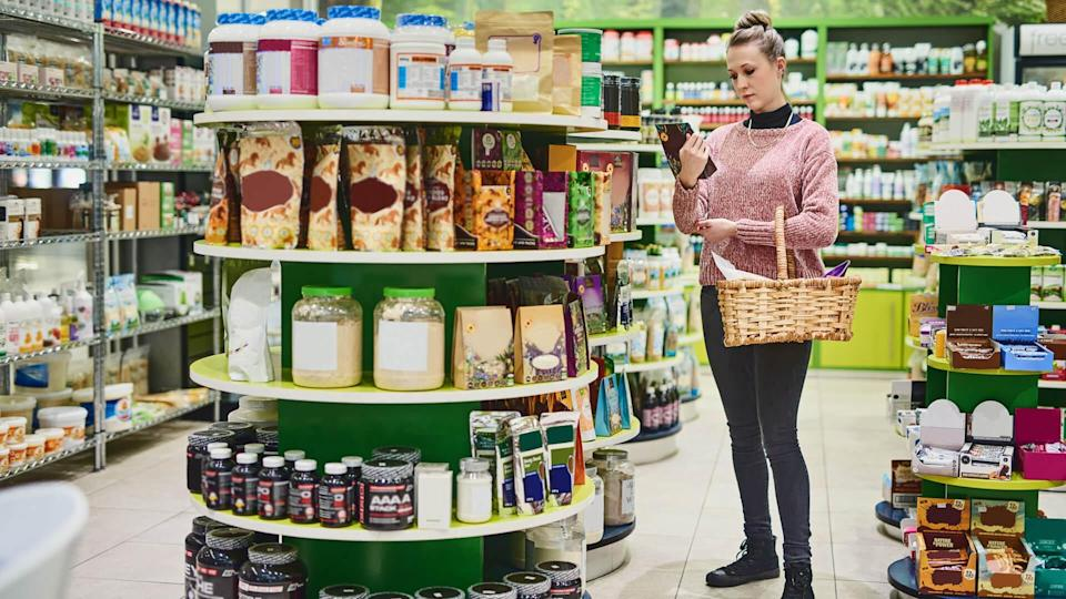 Shot of a young woman browsing for goods on the shelves in a health store.