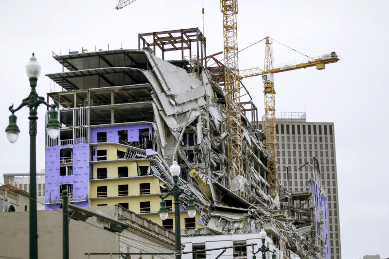 Debris hangs on the side of the building after a large portion of a hotel under construction suddenly collapsed in New Orleans on Saturday, Oct. 12, 2019. Several construction workers had to run to safety as the Hard Rock Hotel, which has been under construction for the last several months, came crashing down. It was not immediately clear what caused the collapse or if anyone was injured.  (Scott Threlkeld/The Advocate via AP)