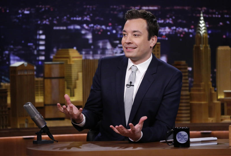 "FILE- In this Feb. 18, 2014 file photo released by NBC, host Jimmy Fallon is seated at his desk during ""The Tonight Show Starring Jimmy Fallon,"" in New York. Fallon, a New Yorker who wanted the excitement of the nation's largest city to permeate his show, brought ""The Tonight Show"" back to New York after 40 years on the West Coast. Producing the show in New York also nets NBC a 30 percent tax credit that can save the network more than $20 million a year. (AP Photo/NBC, Lloyd Bishop, File)"