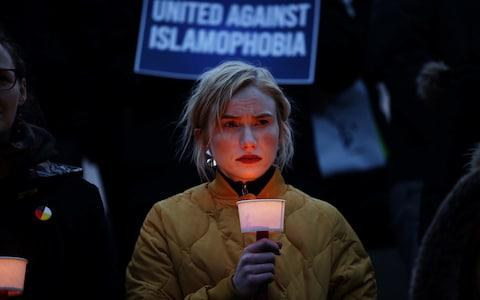 A woman carries a candle at a vigil for victims of the mosque shootings in New Zealand, - Credit: REUTERS
