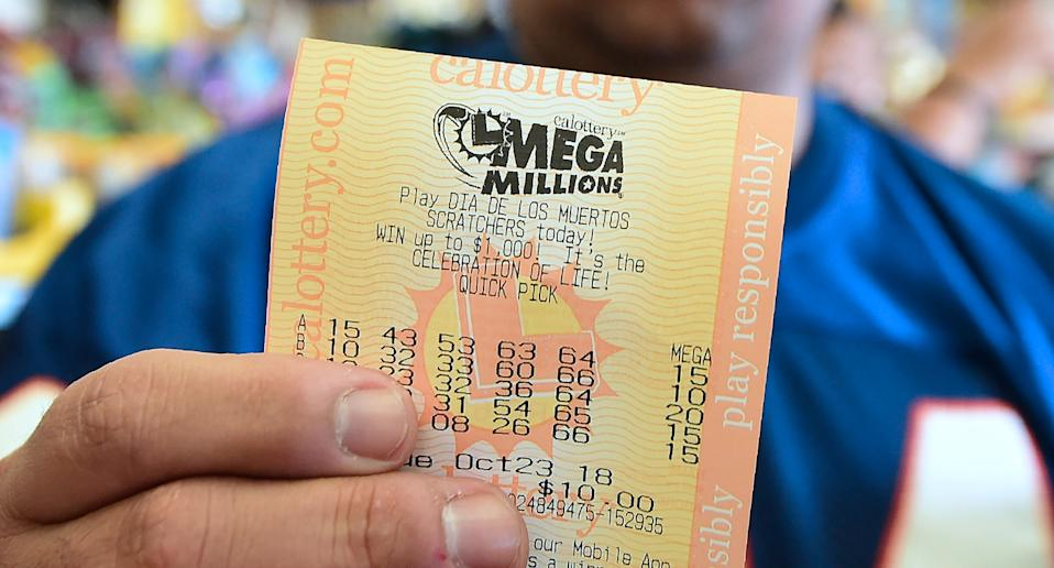 Photo shows a man holding a Mega Millions lotto ticket.