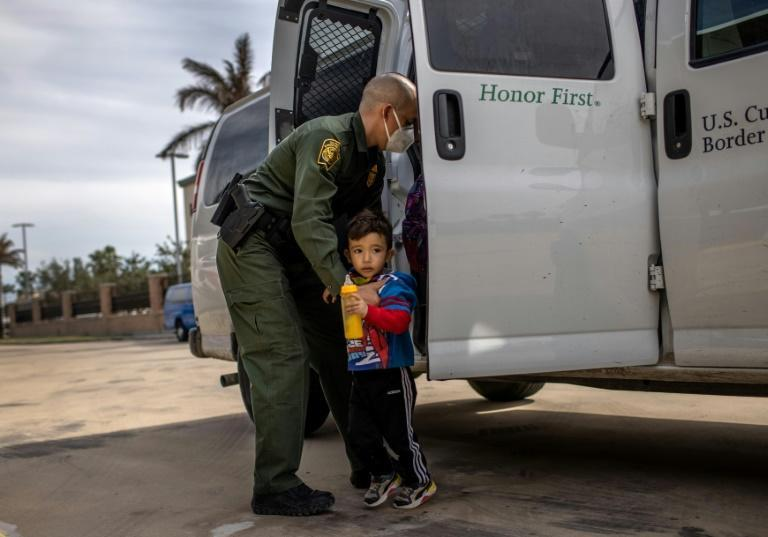 A US border agent transports a child who is seeking asylum to a bus station in Brownsville, Texas, on February 26, 2021