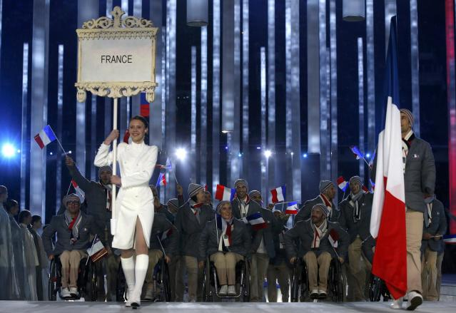 France's flag-bearer Vincent Gauthier-Manuel (R), leads his country's contingent during the opening ceremony of the 2014 Paralympic Winter Games in Sochi, March 7, 2014. REUTERS/Alexander Demianchuk (RUSSIA - Tags: OLYMPICS SPORT)