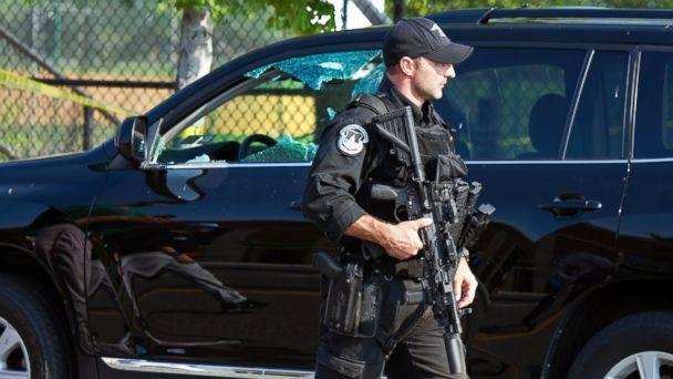 PHOTO: A Capitol Hill Police officer walks past an automobile with the driver's window damaged at the scene of a shooting in Alexandria, Va., June 14, 2017, where House Majority Whip Steve Scalise of La. was shot at a Congressional baseball practice. (Cliff Owen/AP)