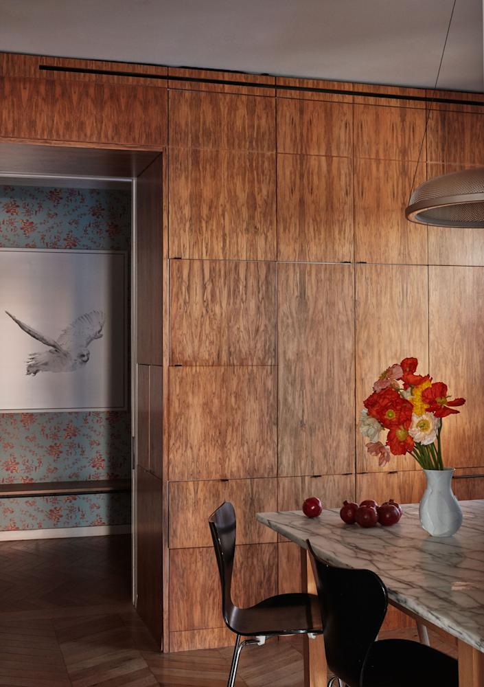 """<div class=""""caption""""> The wood-paneled kitchen, with a view of a Zuckerman photograph and Superflower's Cannonball wallpaper beyond. </div>"""