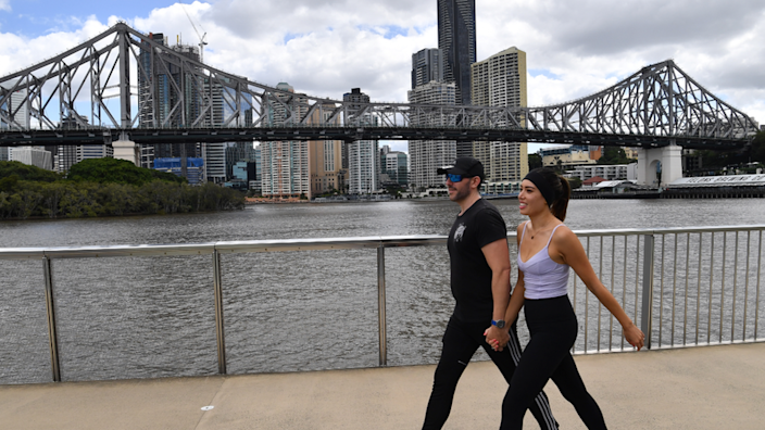A couple walking next to the Brisbane River during the blockade
