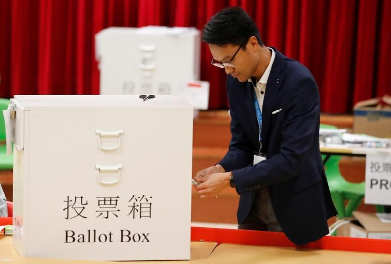 A polling official opens a ballot box to count the votes of the Hong Kong council elections, in a polling station in Hong Kong