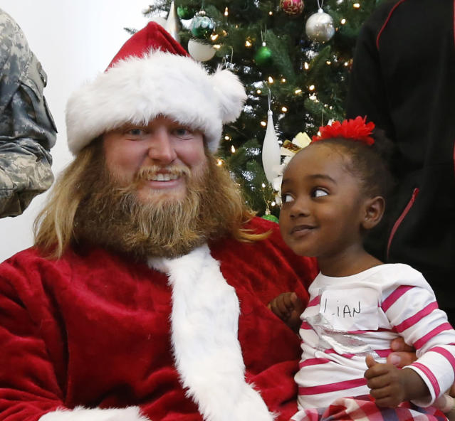 FILE - In this Dec. 4, 2015, file photo, Lian Taylor, 2, of Bayonne, N.J., sits on the lap of New York Jets center Nick Mangold, posing as Santa Claus during the team's holiday party for military families in Florham Park, N.J. Former New York Jets center Nick Mangold has announced his retirement from playing football after 11 seasons in which he established himself as one of the NFL's best at his position. The 34-year-old Mangold announced on Twitter on Tuesday morning, April 17, 2018, that he will sign a one-day contract with the Jets to retire as a member of the team.(AP Photo/Julio Cortez, File)