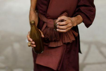 A Buddhist monk holds a glass with a vomit-inducing medication, before giving it to a rehabilitation patient at the detox area at Wat Thamkrabok monastery in Saraburi province, Thailand, February 3, 2017. REUTERS/Jorge Silva