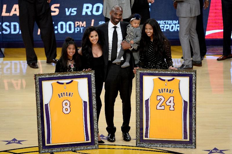 95fa24a8c1a6 Kobe Bryant poses with his family at halftime after both his number 8 and number  24