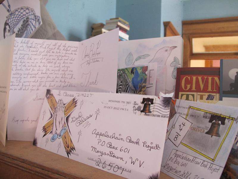 Artwork and thank-you notes from inmates in six states decorate a fireplace mantle at the Morgantown, W.Va., office of the Appalachian Prison Book Project. The volunteer program has so far shipped more than 11,000 free, used books to prisoners in West Virginia, Virginia, Kentucky, Maryland, Ohio and Tennessee. (AP Photo/Vicki Smith)