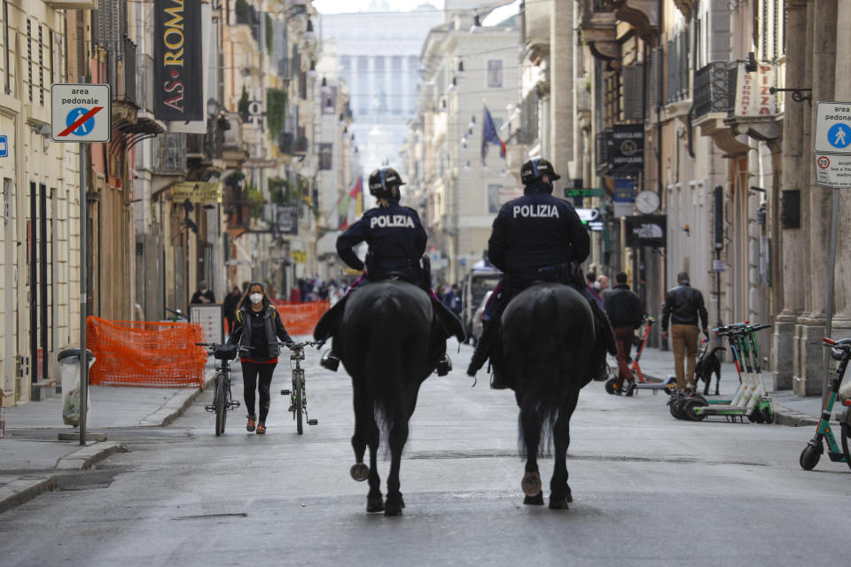 Mounted police officers patrol Via del Corso main shopping street, in downtown Rome, Saturday, April 3, 2021. Italy went into lockdown on Easter weekend in its effort to battle then Covid-19 pandemic. (AP Photo/Gregorio Borgia)
