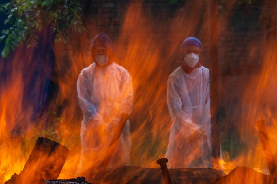 <p>Relatives in protective suits stand next to the burning pyre of a person who died of Covid at a Srinagar crematorium</p> (Getty)