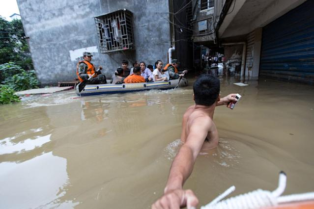<p>Rescuers row as they transfer residents with a boat at a flooded area in Guilin, Guangxi province, China, July 2, 2017. (Photo: Stringer/Reuters) </p>