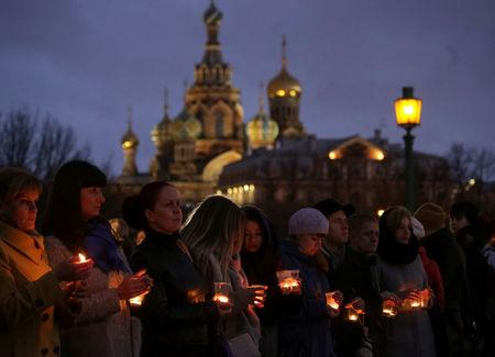 People holds candles to commemorate the victims of a blast in metro train in St. Petersburg, Russia
