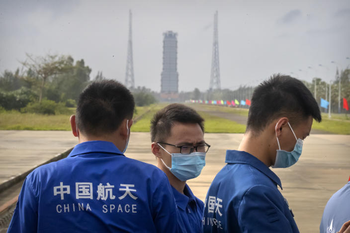 Workers wearing face masks stand near a launch pad at the Wenchang Space Launch Site in Wenchang in southern China's Hainan province, Monday, Nov. 23, 2020. Chinese technicians were making final preparations Monday for a mission to bring back material from the moon's surface for the first time in nearly half a century — an undertaking that could boost human understanding of the moon and of the solar system more generally. (AP Photo/Mark Schiefelbein)