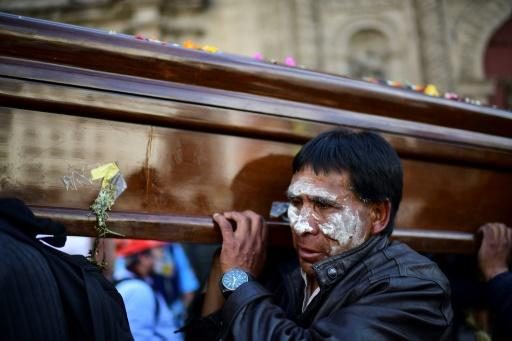 A man carries the coffin of a slain supporter of former president Evo Morales, before riot police fired tear gas to break up the massive funeral procession that turned into an anti-government demonstration