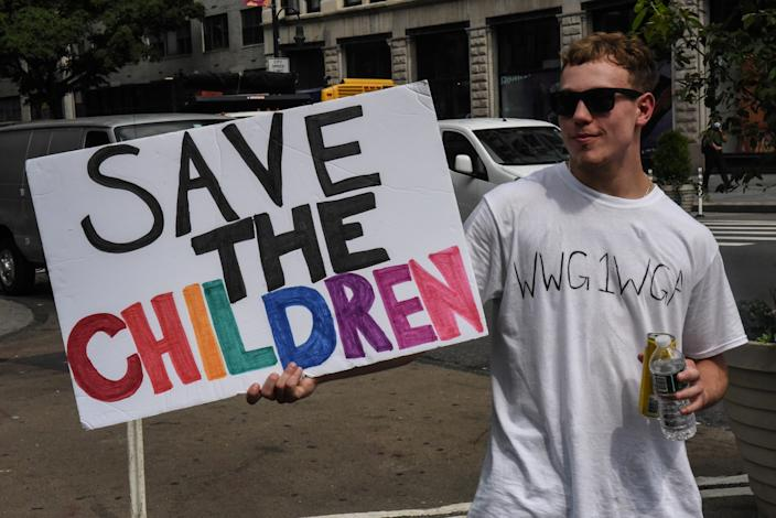 """A person wears a t-shirt with the QAnon slogan """"WWG1WGA,"""" or """"where we go one we go all,"""" while participating in a """"Save the Children"""" rally in New York City on August 12, 2020. By co-opting the """"Save the Children"""" slogan, QAnon has recently spread its baseless conspiracy theories further into the mainstream. (Stephanie Keith/Reuters)"""