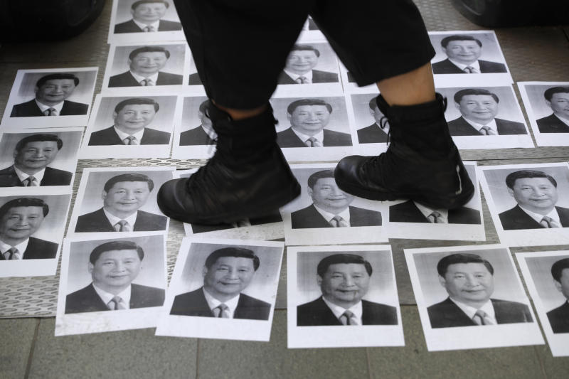 FILE - In this Sept. 28, 2019, file photo, a pedestrian walks past posters of Chinese President Xi Jinping, part of a newly created Lennon Wall, outside the Central Government Complex in Hong Kong. The human rights group Amnesty International says in annual report released Wednesday, Jan. 29, 2020 that while authoritarian controls are increasingly undermining freedoms in Asia, the will to resist such repression is also growing. (AP Photo/Vincent Thian, File)