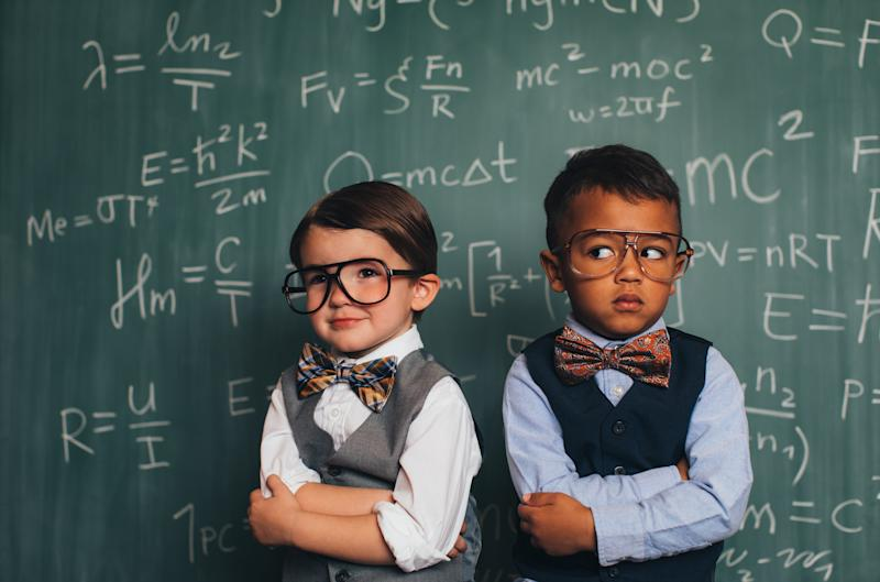 Pictured: Two young boys compare themselves in front of complex maths equation on chalk board. Image: Getty