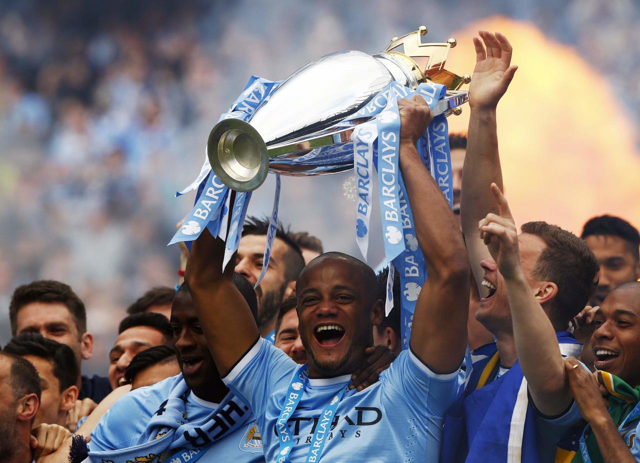 "Manchester City's captain Vincent Kompany (C) celebrates with the English Premier League trophy following their soccer match against West Ham United at the Etihad Stadium in Manchester, northern England May 11, 2014. REUTERS/Darren Staples (BRITAIN - Tags: SPORT SOCCER TPX IMAGES OF THE DAY) FOR EDITORIAL USE ONLY. NOT FOR SALE FOR MARKETING OR ADVERTISING CAMPAIGNS. NO USE WITH UNAUTHORIZED AUDIO, VIDEO, DATA, FIXTURE LISTS, CLUB/LEAGUE LOGOS OR ""LIVE"" SERVICES. ONLINE IN-MATCH USE LIMITED TO 45 IMAGES, NO VIDEO EMULATION. NO USE IN BETTING, GAMES OR SINGLE CLUB/LEAGUE/PLAYER PUBLICATIONS"