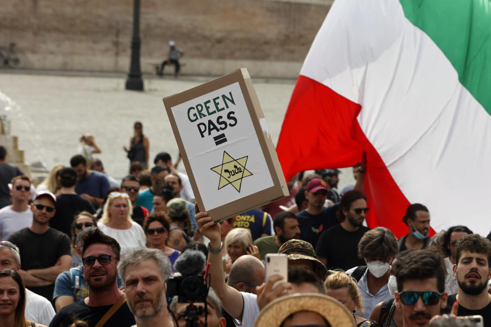 FILE In this , Tuesday, July 27, 2021 file photo, people gather to protest against the COVID-19 vaccination pass in Rome. Protesters in Italy and in France have been wearing yellow Stars of David, like the ones Nazis required Jews to wear to identify themselves during the Holocaust. Some carry signs likening vaccine passes to dictatorships. (AP Photo/Riccardo De Luca, File)