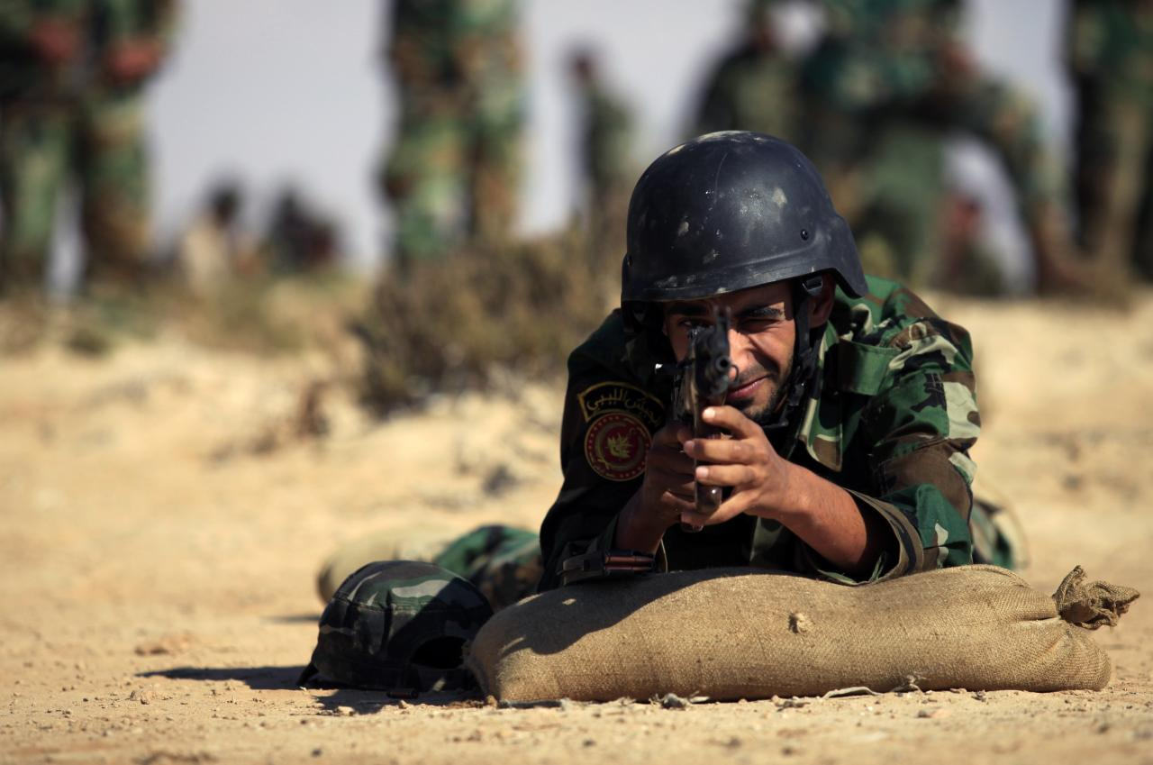 A trainee soldier from the Libyan army takes aim at a target during their graduation exam in Geminis October 30, 2013. The trainees form the first batch of graduates who enlisted after the 2011 Libyan revolution. REUTERS/Esam Omran Al-Fetori (LIBYA - Tags: MILITARY)
