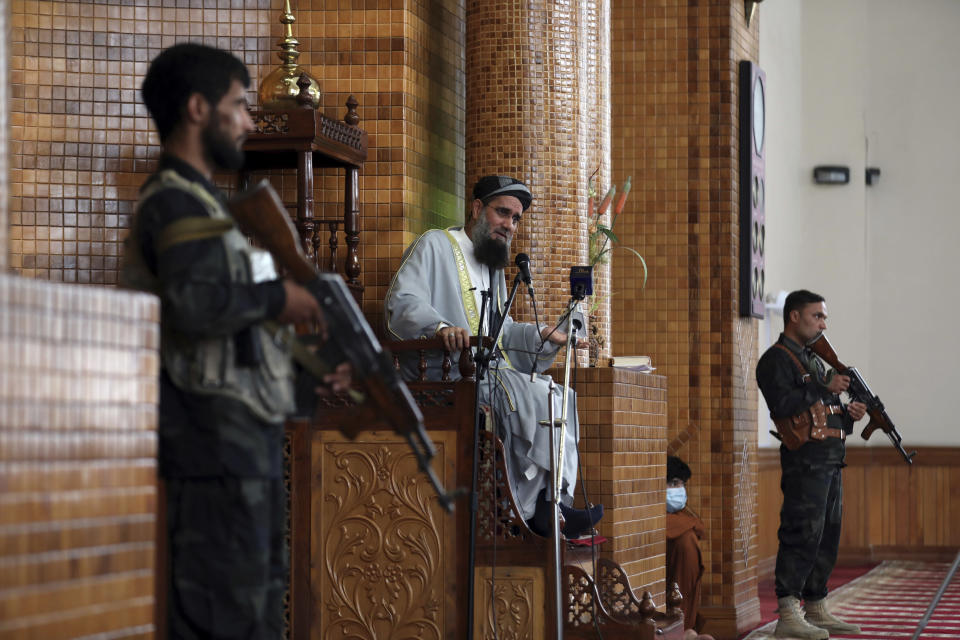 """Flanked by armed security, a cleric consults people in a mosque during Eid al-Adha prayers in Kabul, Afghanistan, Tuesday, July 20, 2021. Eid al-Adha, or """"Feast of the Sacrifice,"""" commemorates the Quranic tale of Prophet Ibrahim's willingness to sacrifice his son as an act of obedience to God. (AP Photo/Rahmat Gul)"""