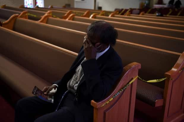It's been a year of lonely grieving. Texas man Samuel Emanuel reacts at the Feb. 13 funeral of his son Samuel Emanuel Jr., 55, who died from the coronavirus.