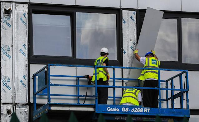 <p>Workers remove cladding from Whitebeam Court, in Pendleton, Manchester, Monday June 26, 2017. The list of high-rise apartment towers in Britain that have failed fire safety tests grew to 60, officials said Sunday, revealing the mounting challenge the government faces in the aftermath of London's Grenfell Tower fire tragedy. (Photo: Peter Byrne/PA via AP) </p>