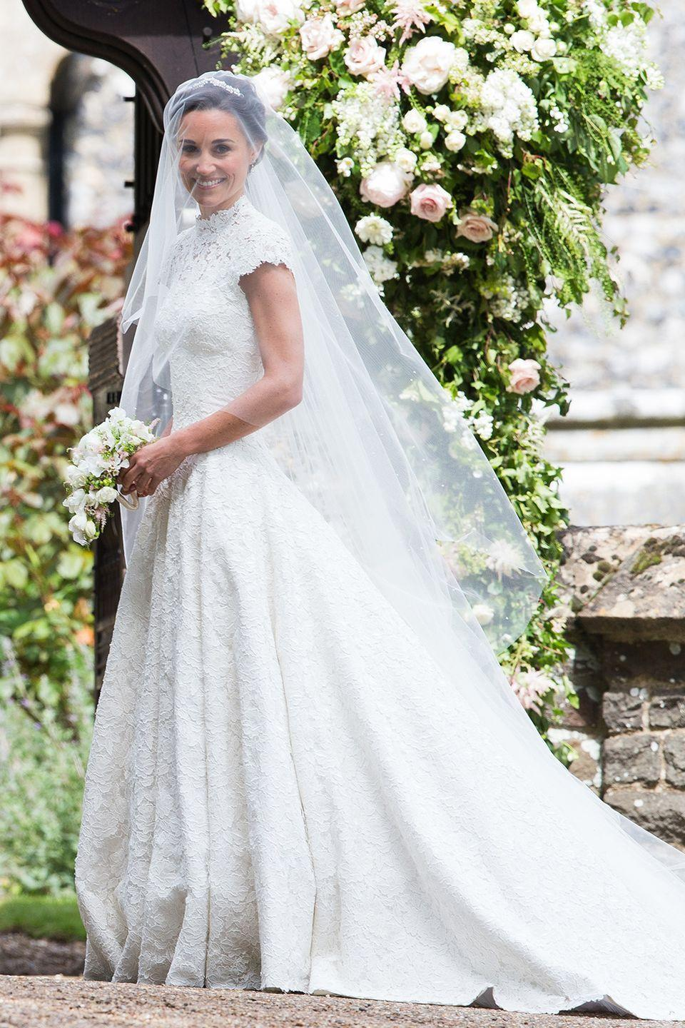 """<p>Pippa wore a custom Giles Deacon wedding gown with short sleeves that showed off her crazy-toned arms. The high lace neck and train drew comparisons to older sister Kate's 2011 wedding gown.</p><p><strong>RELATED</strong>: <a href=""""https://www.goodhousekeeping.com/life/news/g4368/pippa-middleton-wedding-photos/"""" rel=""""nofollow noopener"""" target=""""_blank"""" data-ylk=""""slk:Pippa Middleton's Wedding in Photos"""" class=""""link rapid-noclick-resp"""">Pippa Middleton's Wedding in Photos</a></p>"""