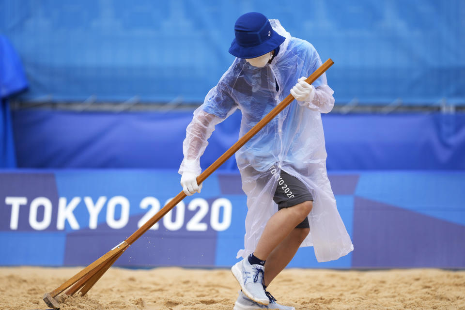 A member of the grounds crew rakes the sand before a men's beach volleyball match at the 2020 Summer Olympics, Tuesday, July 27, 2021, in Tokyo, Japan. (AP Photo/Petros Giannakouris)
