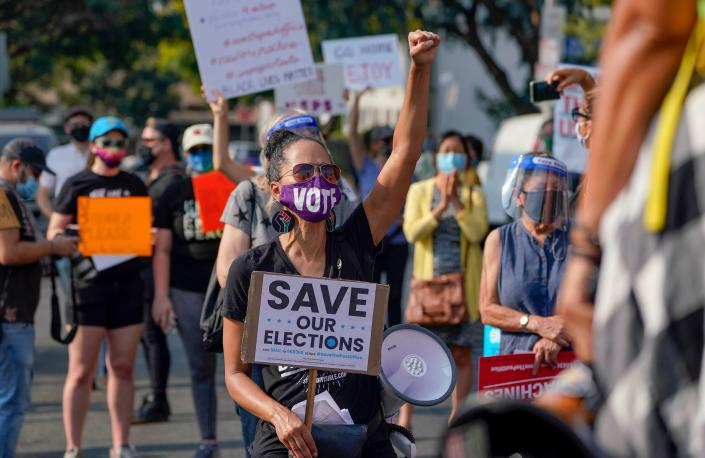 "Protesters hold a ""Save the Post Office"" demonstration outside a USPS location in Los Angeles on Aug. 22. (Photo by Kyle Grillot/AFP via Getty Images)"