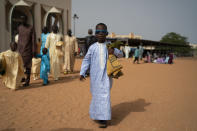 A Senegalese youth walks away from the Mosque after attending the Eid al-Adha prayer in Dakar, Senegal, Wednesday, July 21, 2021. People attend Tabaski celebrations as COVID-19 cases surge in the West African nation. (AP Photo/Leo Correa)
