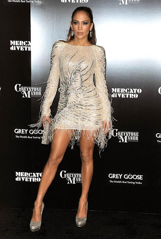 "Hours after embarrassing herself on stage at the American Music Awards -- in a tacky, bedazzled bodysuit -- Jennifer Lopez rebounded at an after party. The diva extraordinaire oozed glamour as she entered West Hollywood's Greystone Manor Supperclub in a beaded, ostrich feather-adorned Emilio Pucci mini. Her sparkling accessories included statement earrings, a metallic clutch, and Jimmy Choo ""Eros"" pumps. (11/20/2011)"