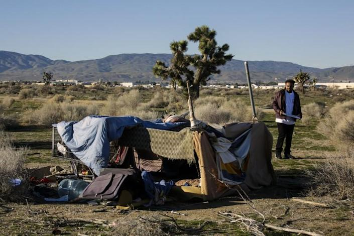 LANCASTER, CA JANUARY 28, 2016 -- On the third and final day of the homeless census Derrick Chambers checks out an encampment in an open area of Southern part of Lancaster while documenting their number in the area. Thousands of volunteers are counting more than 95 percent of the census tracts in the region from 150+ deployment sites. Organizers hope the data will give an accurate picture of the state of homelessness in Los Angeles and helps advocate for funding and allocation of resources where they will have the greatest impact. (Irfan Khan / Los Angeles Times)