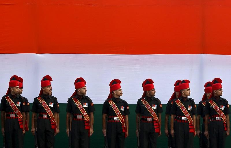 Indian soldiers stand guard in front of an India's national flag tri-colours during the full-dress rehearsal for India's Independence Day celebrations at the historic Red Fort in Delhi, India, August 13, 2015. India commemorates its Independence Day on August 15. REUTERS/Adnan Abidi      TPX IMAGES OF THE DAY      - GF10000172476