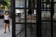A woman wearing protective face mask walks outside of a closed cafe amid COVID-19 pandemic restrictions government in central capital Nicosia, Cyprus, Thursday, May 6, 2021. Cyprus has unveiled a phased rollback of COVID-19 lockdown restrictions over the next month including a shortened curfew and a reopening of all schools next week, but will enforce the compulsory display of proof of vaccination, virus testing or convalescence from the disease in areas were people gather in numbers, including restaurants and churches. (AP Photo/Petros Karadjias)