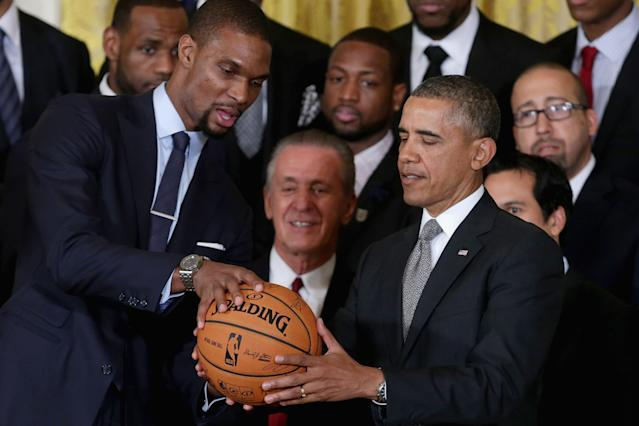 WASHINGTON, DC - JANUARY 14: National Basketball Association 2012-2013 champion Miami Heat player Chris Bosh (L) presents President Barack Obama with a signed basketball during an event at the White House January 14, 2014 in Washington, DC. This is the second year in a row the team won the championship and made a trip to 1600 Pennsylvania Avenue. (Photo by Chip Somodevilla/Getty Images)